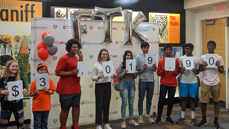 BuckeyeThon participants holding sign reading $3,019.90